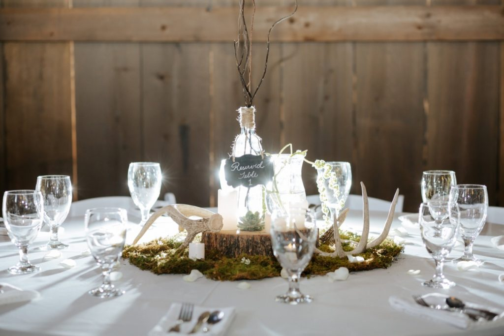 A table top centerpiece made of a wooden base, surrounded by faux grass and topped by a plant in a glass bottle All glow-y because of the light. Eagle Dance Ranch