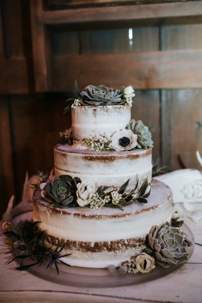 A traditional Bride's cake made more rustic by flowers and wood-like textures.