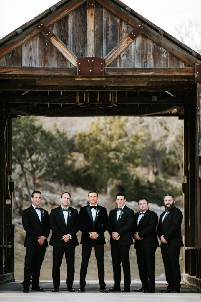 A groom and 4 groomsmen standing at the creaky covered bridge in Eagle Dance Ranch