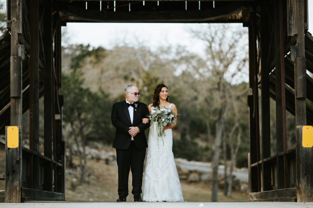 A bride and her father stroll the creaky old covered bridge in Eagle Dance Ranch.