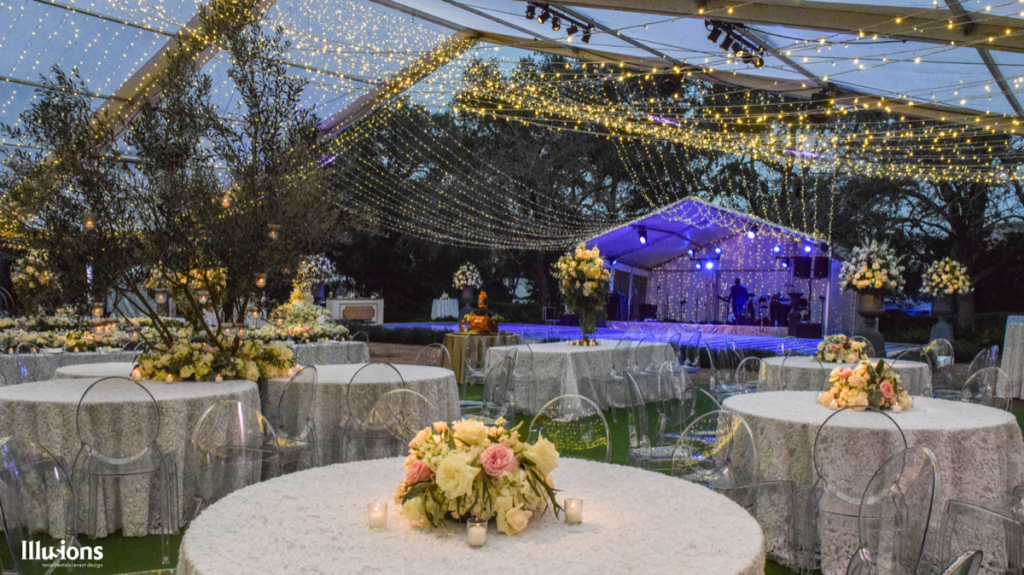 Illusions Tents, Rentals, & Design tops this outdoor reception with a dazzling array of lights.
