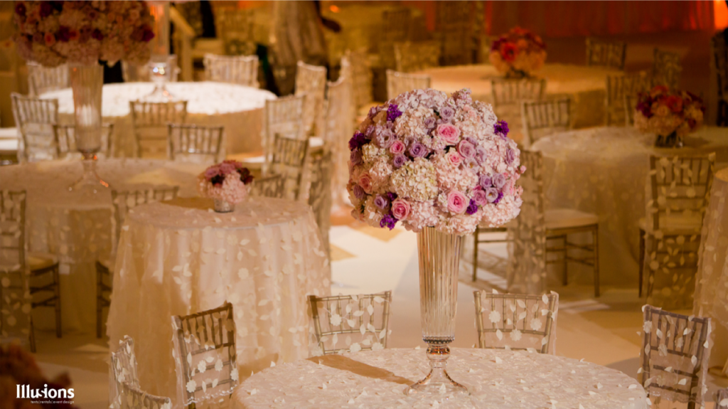 Even a simple rose assortment table centerpiece becomes elegant due to the dsign by Illusions Tents, Rentals, & Design.