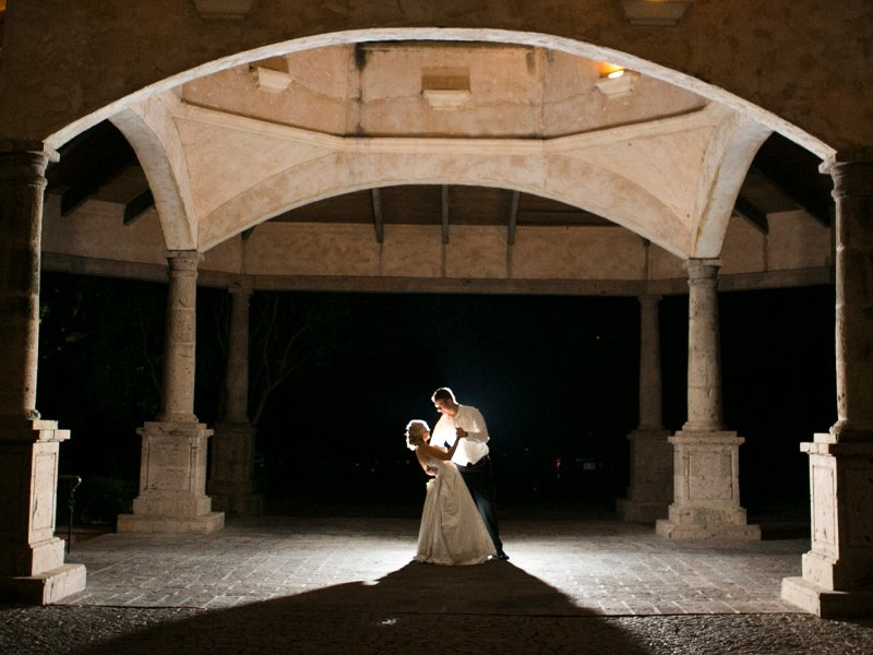 A couple dancing by themselves under the gondela-like structure at The Dominion Country Club