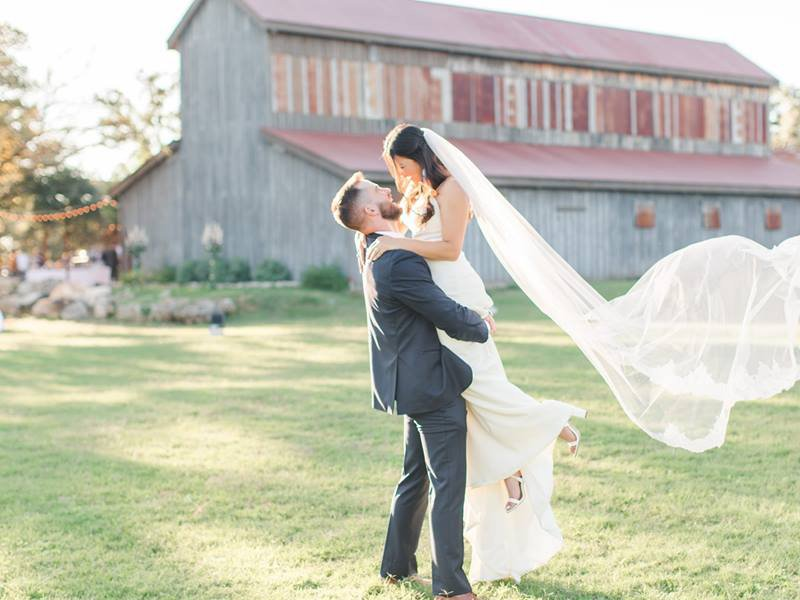 A groom lifting the Bride in front of the barn at Eagle Dance Ranch