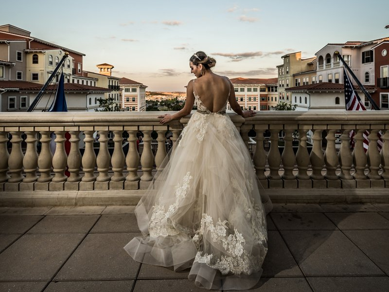 A bride contemplates her upcoming event standing on the balcony overlooking buildings. At The Eilan Hotel Resort and Spa