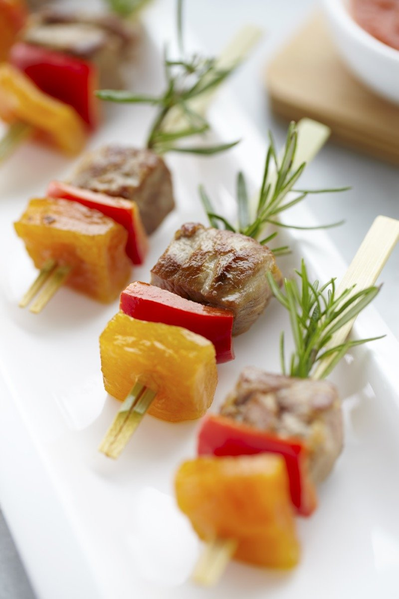 Close up view of meat & fruit shish kebabs