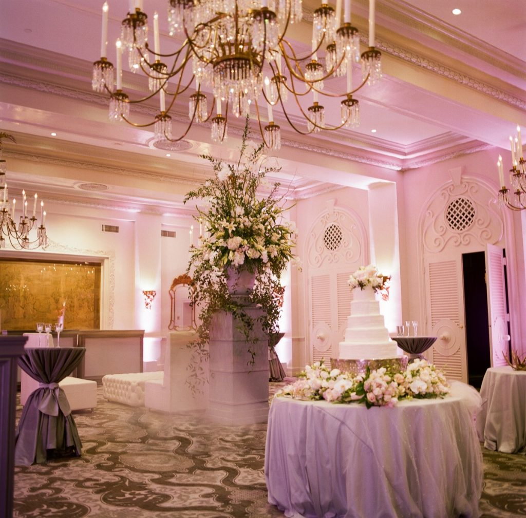 Alamo Plants & Petals demonstrates a room filled with floral arrangements, centering on a small pillar with a ginormous and elegant flowerpot reaching far up to the ceiling.