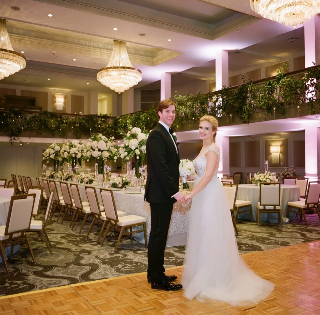 Alamo Plants & Petals presents a future mr. and Mrs. standing in front of a wonderful tabletop decorated lavishly at the St. Anthony hotel ballroom.