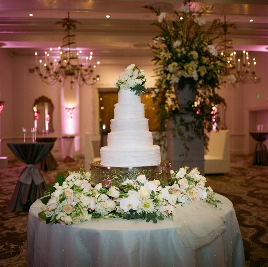 Alamo Plants & Petals presents a bride's cake surrounded by white and yellow roses.