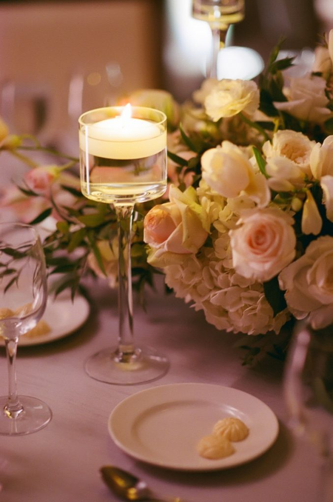 Alamo Plants & Petals shows a closeup of a yellow candle in a wineglass holder amongst the yellow and blush flowers.