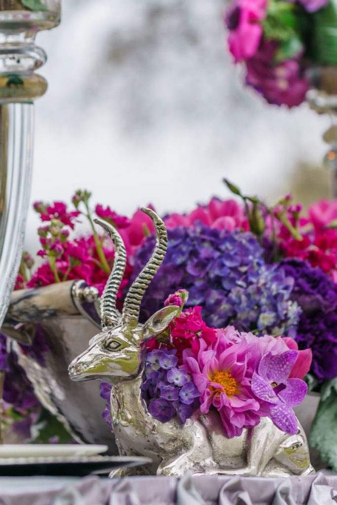 Alamo Plants & Petals presents a silver antelope statuette that is the flowerpot for lavender, purple and deep magenta flowers.