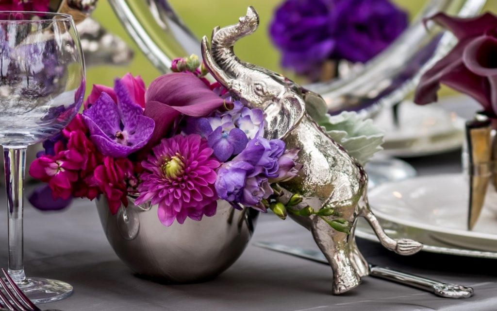 Alamo Plants & Petals shows a simple silver elephant statuette can enhance the flowerpot made up of brightly colored lavender, purple, and deep magenta flowers.