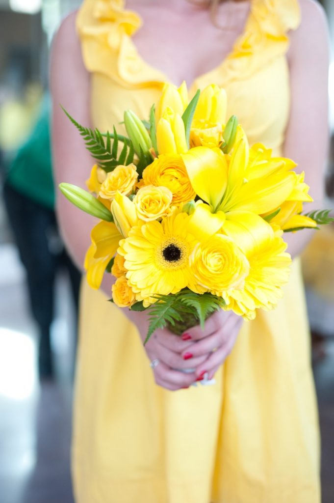 Alamo Plants & Petals presents a woman in yellow holding a bouquet of yellow flowers