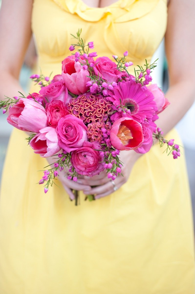 Alamo Plants & Petals presents a woman in yellow holding a bouquet of magenta-hued flowers