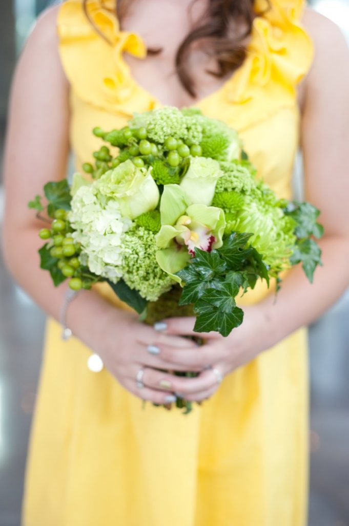 Alamo Plants & Petals presents a woman in yellow holding a bouquet of green-hued flowers