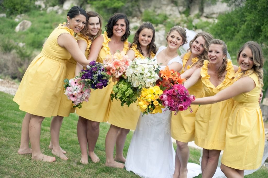 Alamo Plants & Petals presents yellow-clad bridesmaid - and one bride - holding mulyi-colored flowers.