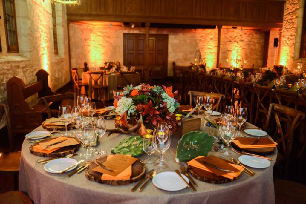 Alamo Plants & Petals shows a tabletop ladened with orange and brown, with an orange-brown-green-and red floral arrangement in the center.
