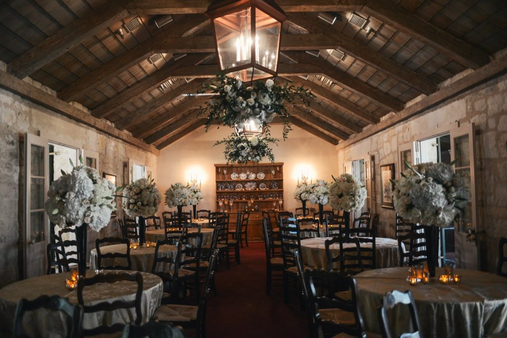 Alamo Plants & Petals shows us a room of tables and chairs with long-stemmed balls of white roses.