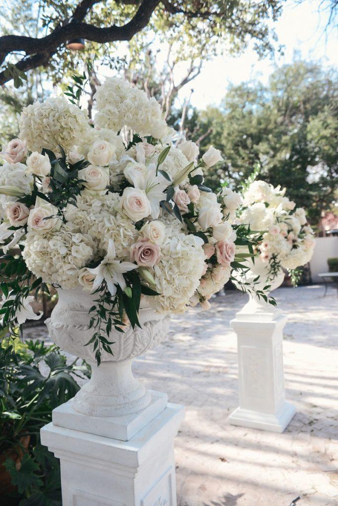 Alamo Plants & Petals white roses and dahlias adorn the outdoor masonry flower pots.
