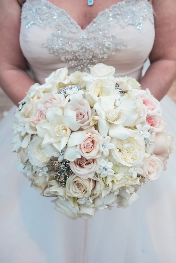 Alamo Plants & Petals special round bouquet of white and blush roses being held by a woman in white.