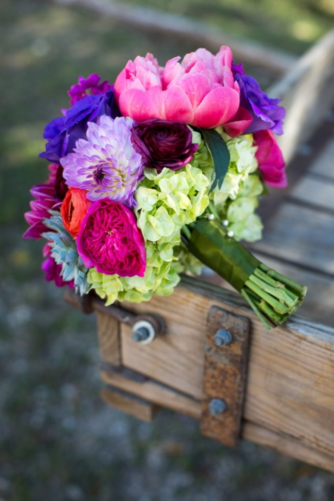 Alamo Plants & Petals bouquet of blush, lavender, and purple flowers sitting on a rustic wooden frame.