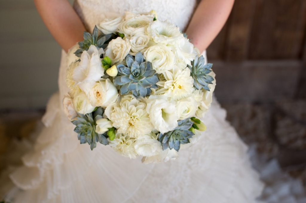 Alamo Plants & Petals shows a round bouquet of yellow and light green flowers being held by the bride.