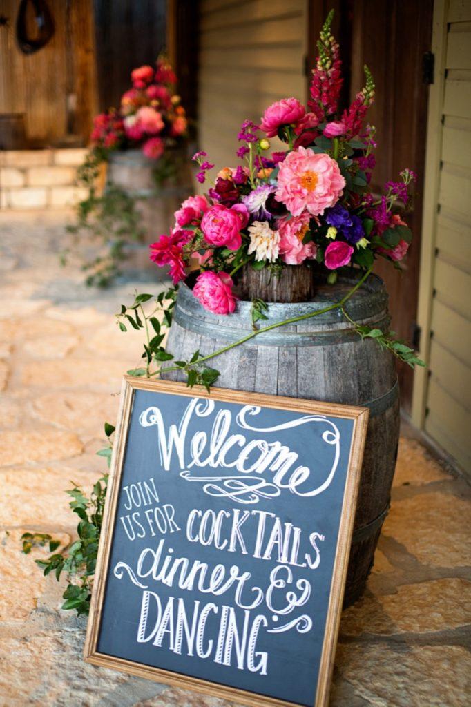 Alamo Plants & Petals adorns a rustic barrel with a wooden bowl of bright wonderful flowers.