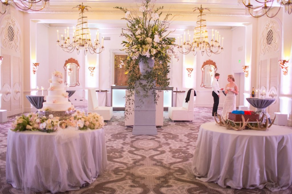 Alamo Plants & Petals shows us a bright lavenderish room with bridal cake and tabletops with a man and woman off to the right side, talking.