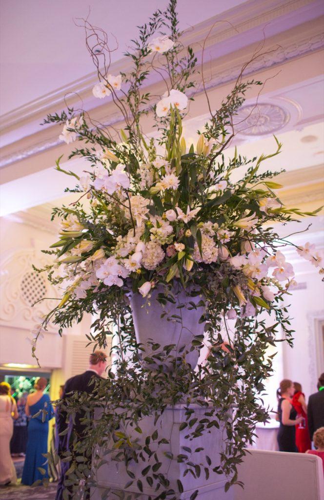 Alamo Plants & Petals shows us a resplendent floral arrangement in a vase that overlooks the people around it.