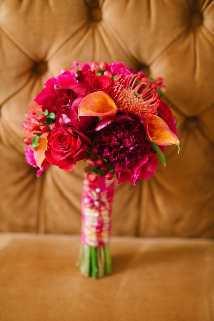 Alamo Plants & Petals presents a brightly colored bouquet with red, fusha, roses and other plants.