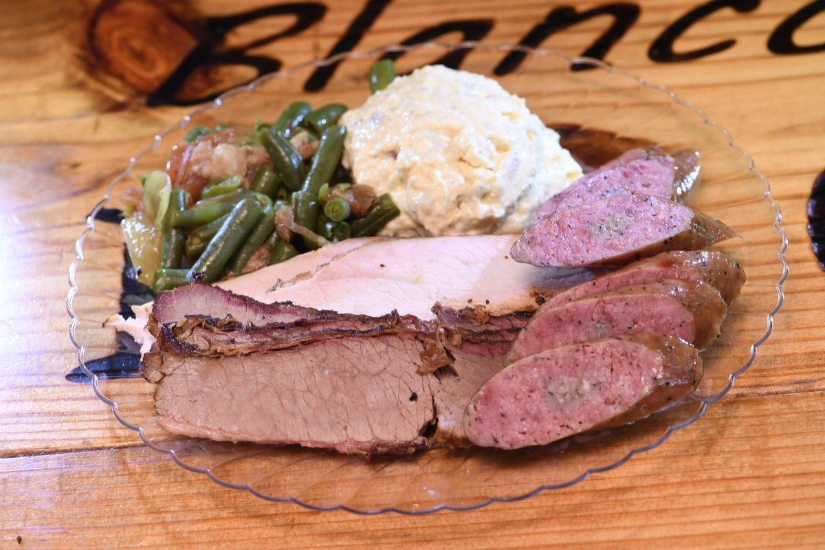 Blanco BBQ serves a three course meak of BBQ, Pork sausages, turkey with a smattering of green beans and a dollop of mashed potatoes. Yum!