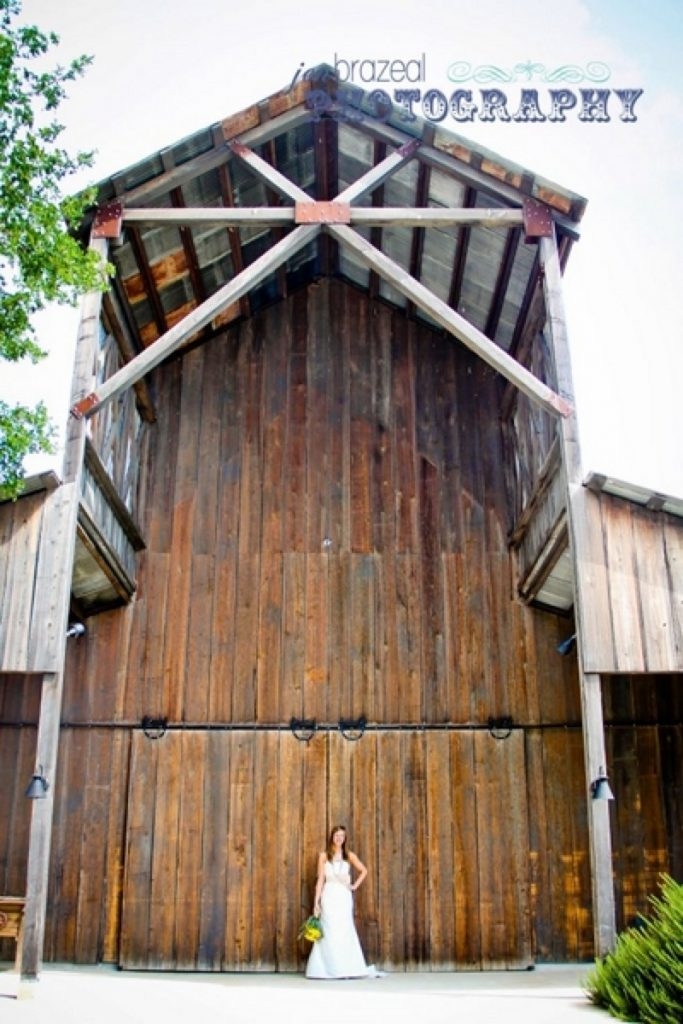 A bride, who looks so small next to the Eagle Dance Ranch big barn.