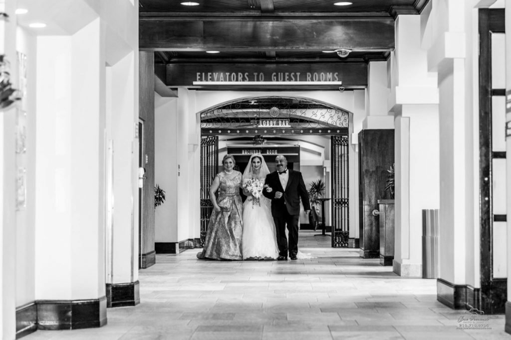 A black and white photograph of the Bride being escorted by her mom an dad.