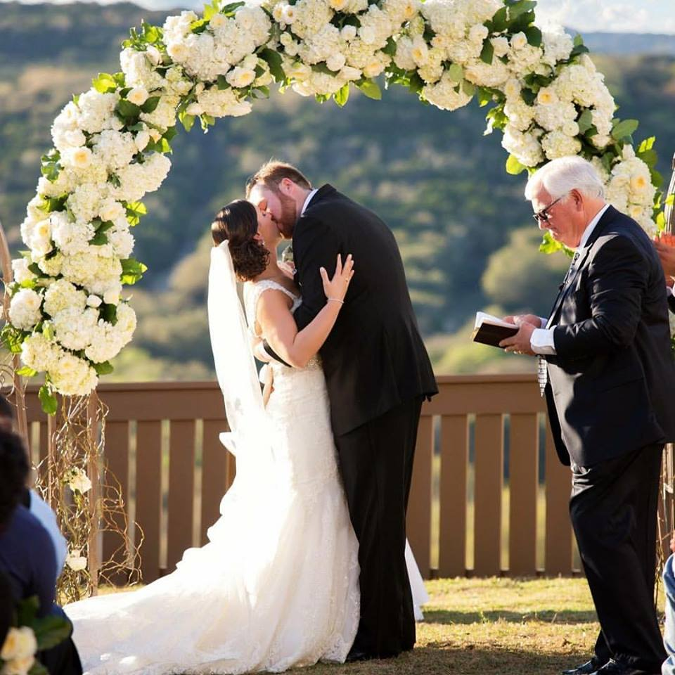 Evember Floral & Event Design- a couple kissing at the alter