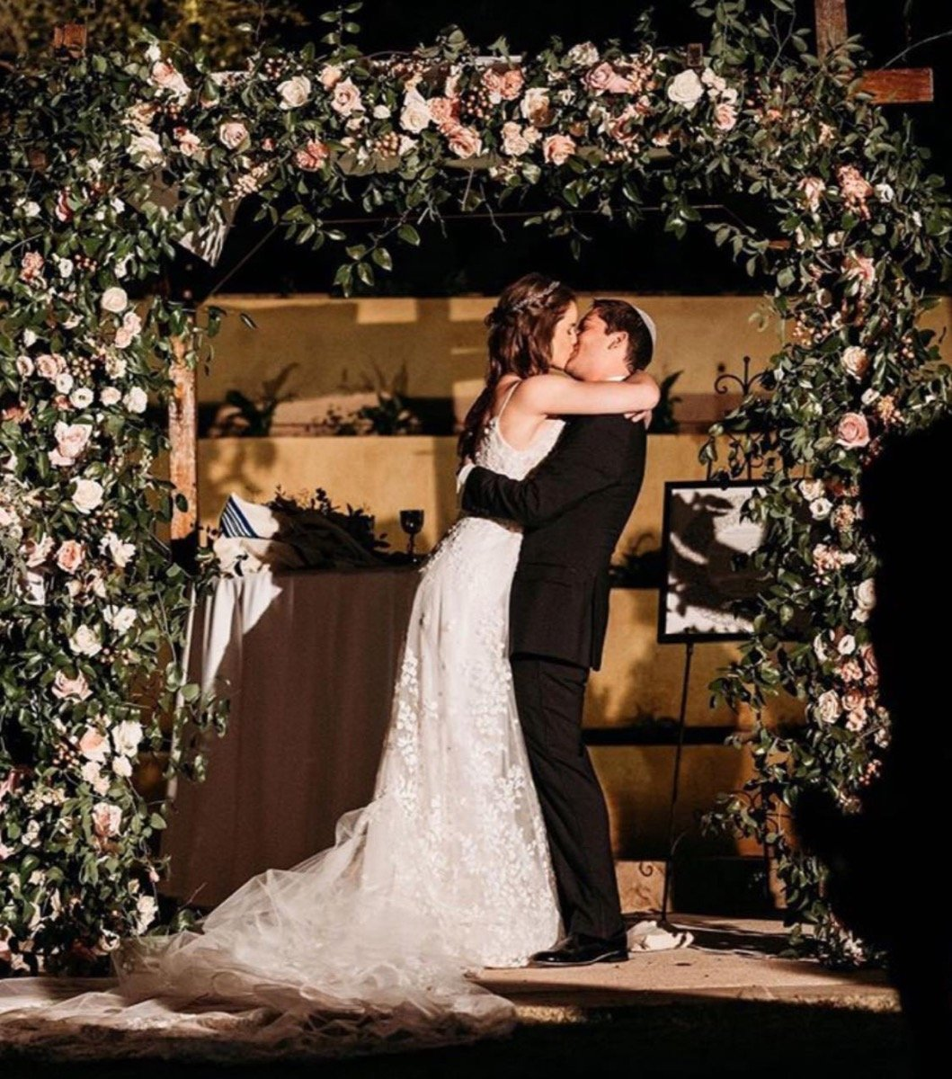 A groom and Bride kiss during their ceremony as husband and wife. They are framed by a Freesia Designs designed alter.