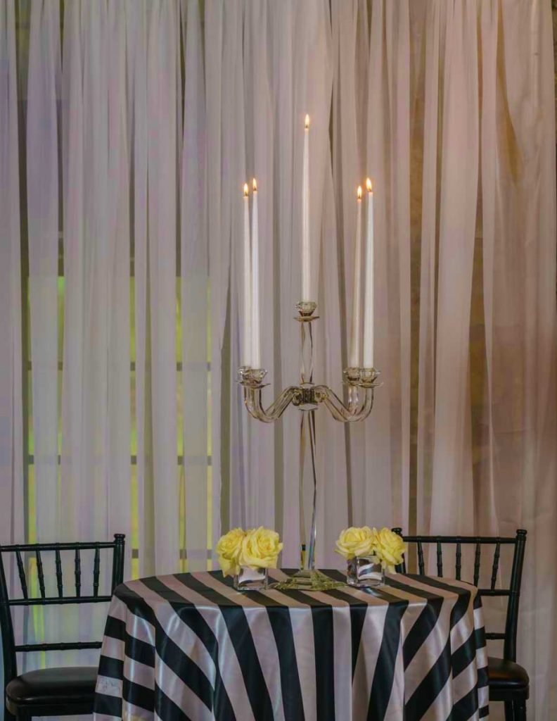 This simple quint-candleabra is enhanced by the stricking silver-and-black design, by Illusions Rentals, & Design