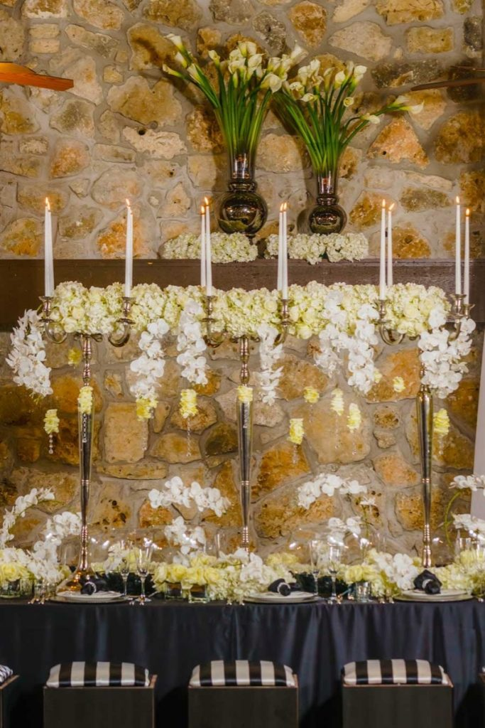 A wonderful design by Illusions Tents, Rentals, & Design of the wedding party banquet table. Candles are placed very high and the florals compliment the florals on the table itself!
