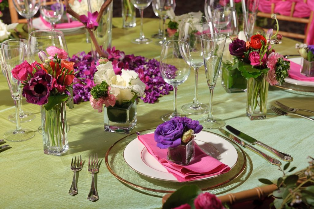 A close-up of a green topped table, with magenta accessories as produced by Illusions Tents, Rentals, & Design!