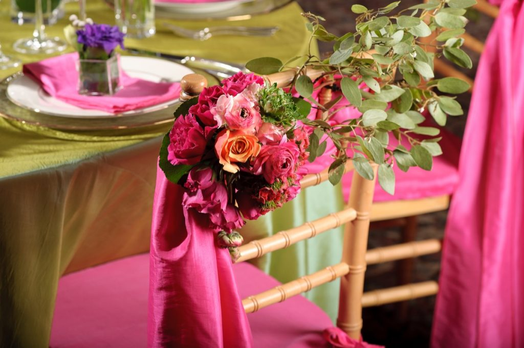 A close-up of the magenta florals on the back of the chairs as done by Illusions Tents, Rentals, & Design