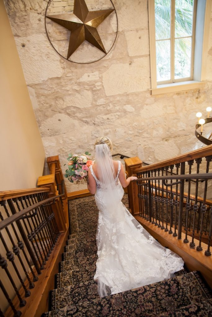 The Bride walks down the luxurious staircase toward her wedding.