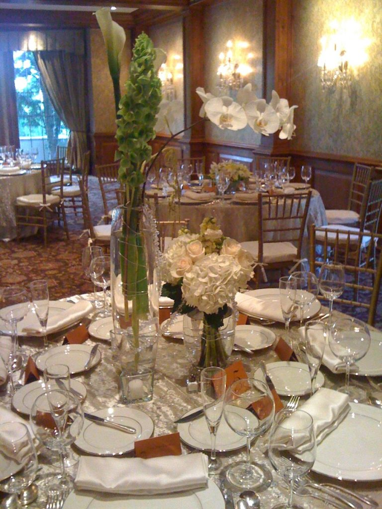 Illusions Tents, Rentals, & Design gives us a look at a striking centerpiece set on a muted background of white plates and napkins.