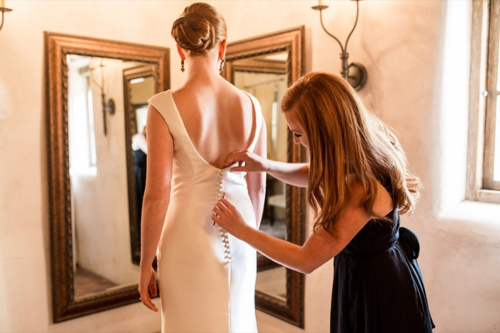 A final check on the dress before the bride gets married at Lost Mission.