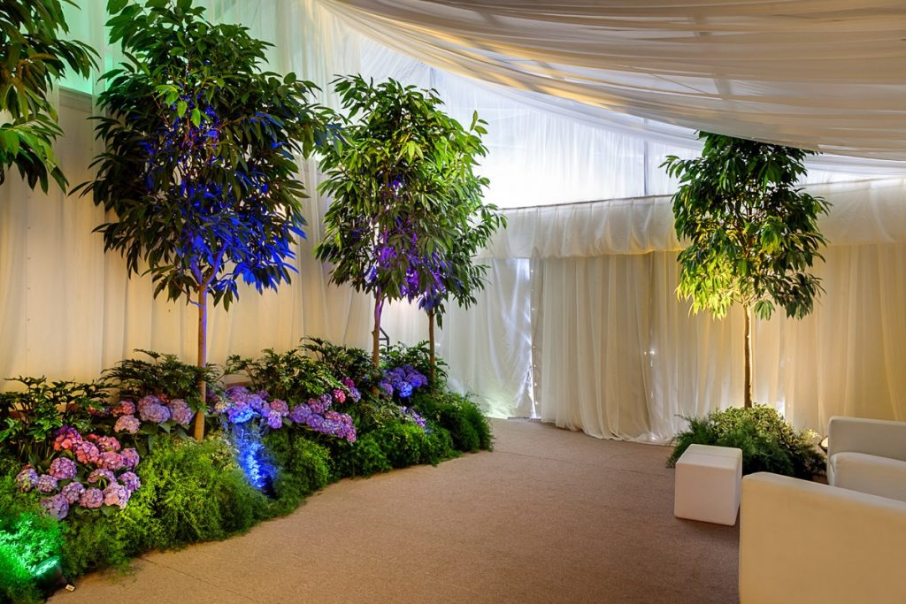 A magical Illusions Tents, Rentals, & Design moment with billowing white drapery frame a virtual forest teaming with color!