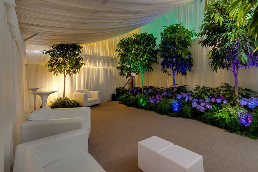 Another shot of Illusions Tents, Rentals, and Event Design virtual sitting room with white billowing drapery surrounding a small patch of magical forest.