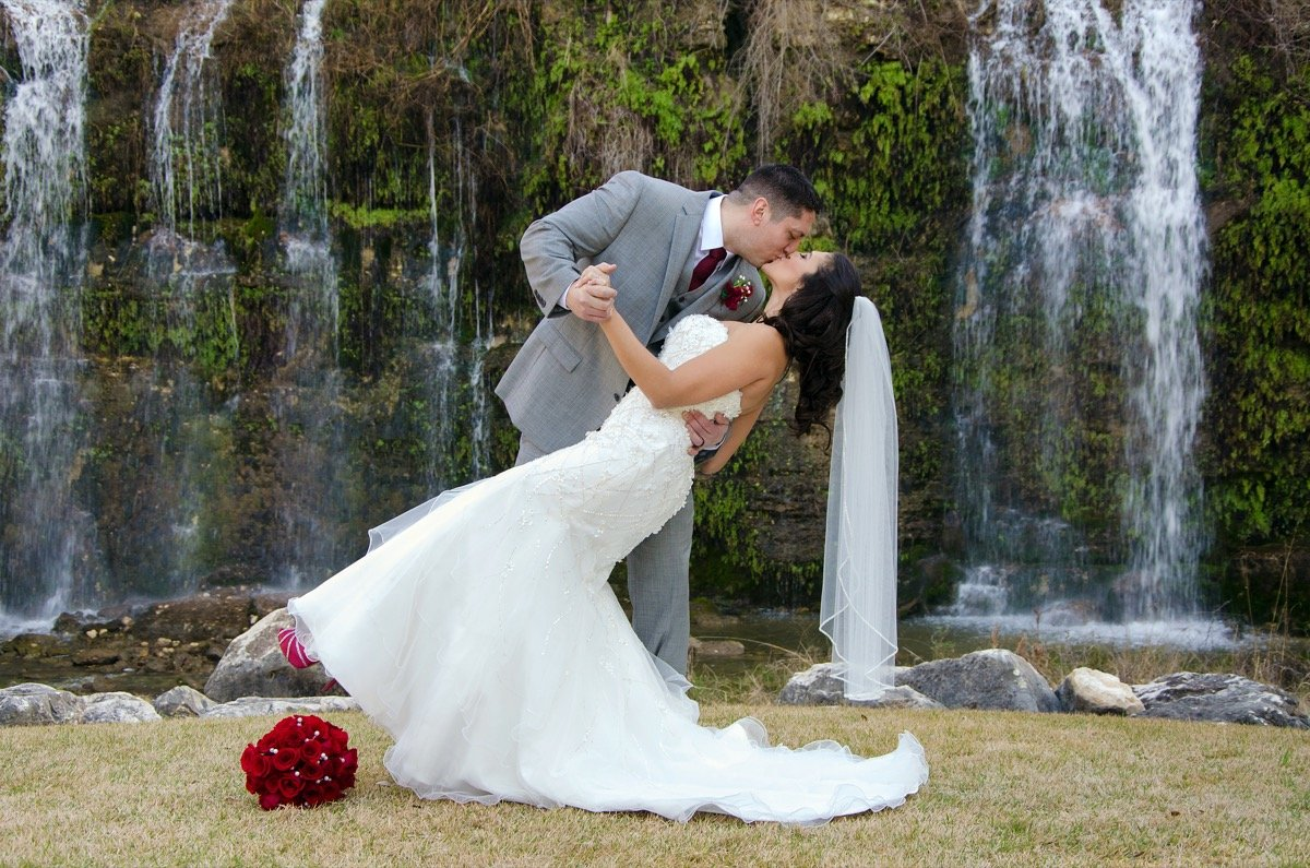 a dramatic kiss from the groom to the bride in front of the waterfall at Canyon Springs Golf Course!