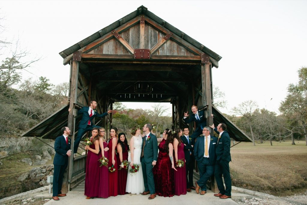 The entire wedding party clowing around at the Eagle Dance Ranch creaky old bridge.
