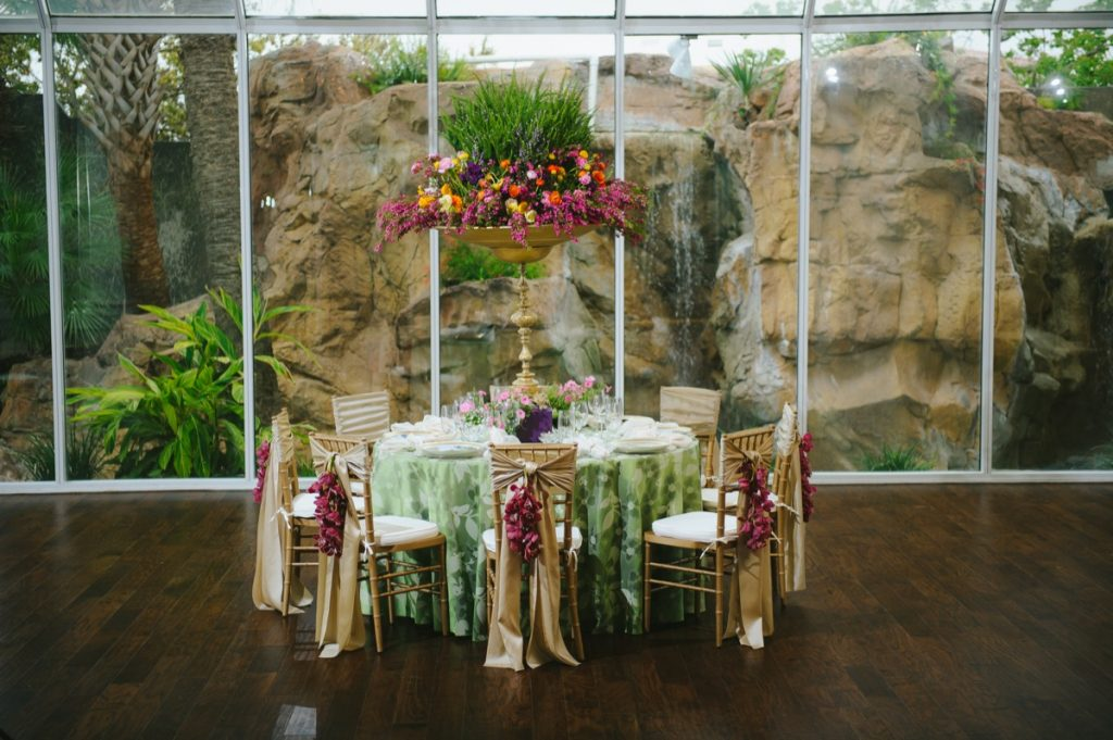 Set in the Crystal Room of the Old San Francisco Steakhouse is a delicate green tablecloth-laden table with a large centerpiece filled with brilliant colored flowers courtesy of Illusions Tents, Rentals & Designs!