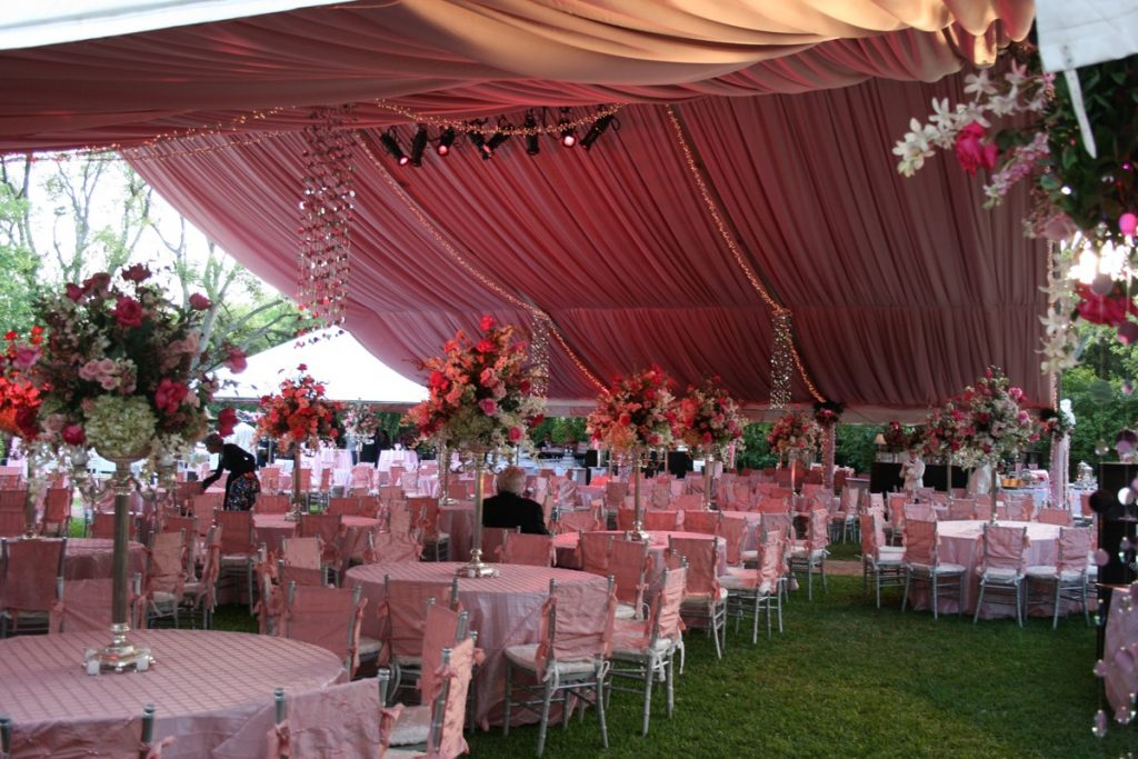 Illusions Tents, Rentals, & Designs engulfs this outdoor space with a tent of reddish brown covering an awesome banquet space of red, brown, green, and white