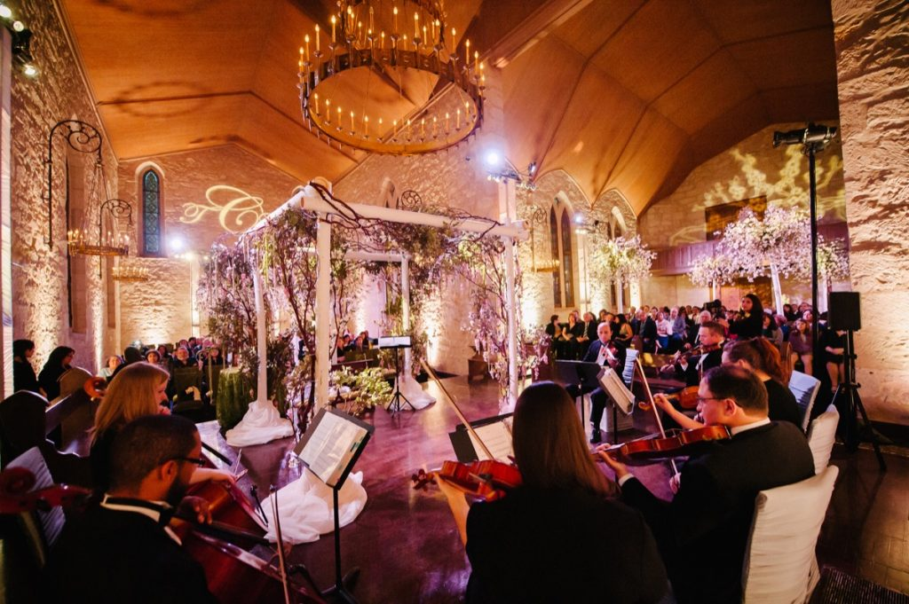 A ring of musicians play before a cascading envelope of a lighted alter, awaiting the wedding.