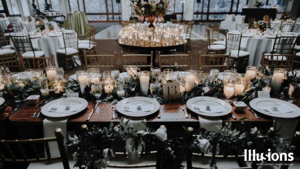 A bare-top table for the wedding party brings to memory olden days where the food would be delicious and the talk would be ribald! Thank you Illusions Tents, Rentals, and Designs!